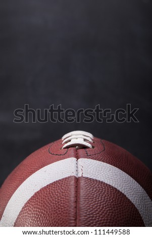 An American football with a chalkboard in the background for copy-space.