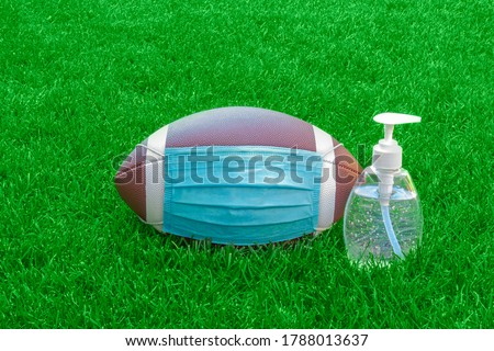 An American Football with a facemask and hand sanitizer on field with green grass. Concept Football during pandemic