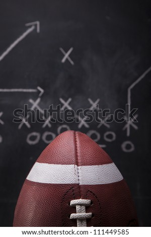 An American football with a play drawn up on a chalkboard in the background.