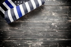 An american police flag thin blue line on a wooden vintage rustic background.
