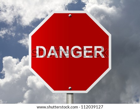 An American road stop sign with word Danger with clouds and sky, Stop it is dangerous