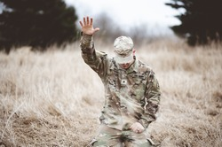 An American soldier kneeling in despair on a grass field with his hand raised above