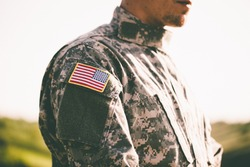 An American soldier looks into the distance at sunset. USA flag on a soldiers hand. United States Army. Veterans Day