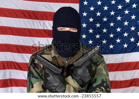 An American stands prepared to protect his country from terrorism with his handguns.