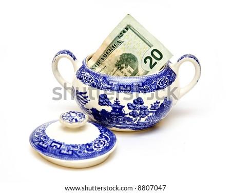 An American twenty dollar bill sticking out of a sugar bowl.  Savings, economy concept. - stock photo