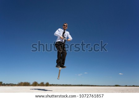 An amusing business concept with a man jumping high on a Pogo Stick.