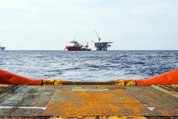 An anchor handling tug boat leaving an offshore oil production platform with a construction vessel moored next to it