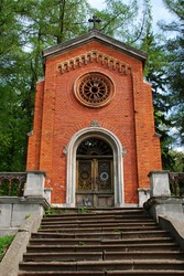 An ancient chapel of red brick. Chapel in the ancient Lychakiv cemetery of Lviv, Ukraine. A staircase leads to it.
