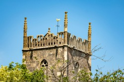 An ancient church spire and trees  against bright blue sky