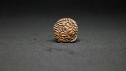 An ancient copper Tamil coin of the Chola dynasty.