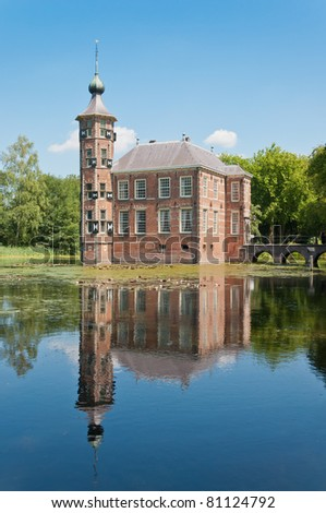 An ancient Dutch castle reflected in the pond. The castle dates from the 15th century. The sky is blue and the water surface is mirror smooth.