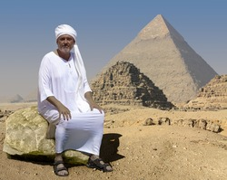 An ancient Egyptian sits on a rock in front of the historic Giza pyramids in Egypt. Right behind him are two little crumbled pyramids. The man is wearing a white robe and a turban.