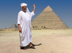 An ancient Egyptian stands in front of the historic pyramids of Giza in Egypt and explains the scenery. He is wearing a white robe and a turban. The man points to the great pyramid with his hand.