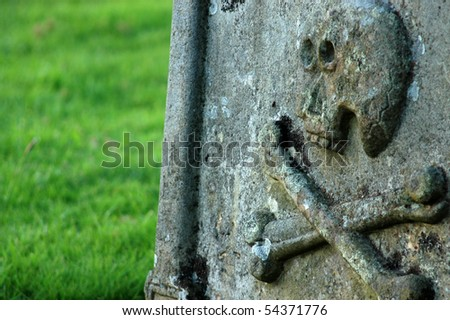 An ancient gravestone with a skull and crossbones