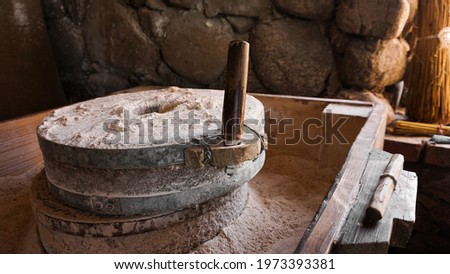 An ancient hand mill made of stones and wood. Flour grinding device. Authentic handicraft Photo stock ©