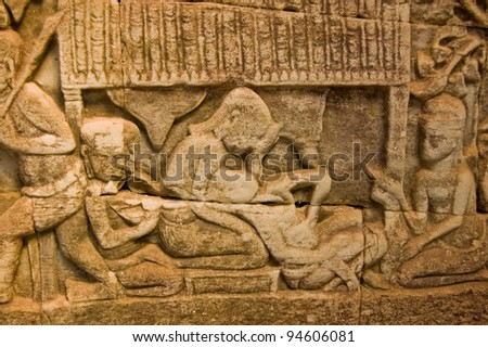 An ancient Khmer bas relief carving showing a woman giving birth.  Wall of Bayon Temple, Angkor Thom, Siem Reap, Cambodia.