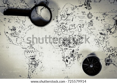An ancient map, a compass and a magnifying glass