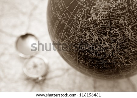 An ancient map of the world with a compass on the backgorund