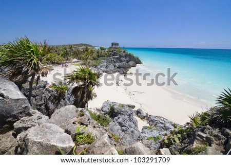 An ancient Mayan ruin overlooking the teal blue waters of the Mexican Riviera beach. Sandy cove with Palm trees. Tourists walking in the distance. Focus is mainly on the foreground rocks and beach.