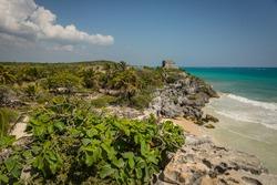 An ancient Mayan ruin overlooks a beautiful sandy beach in Tulum, Mexico