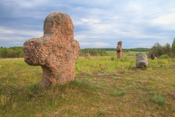An ancient pagan cemetery with stone crosses, a place for rituals, ceremonies and worship. The stones of the Crosses grow out of the ground at the top of the mound.Rock paintings on the stones.