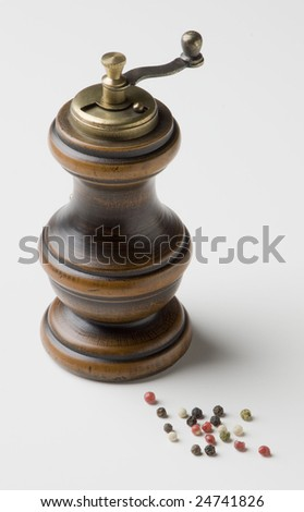 An ancient peppermill with pepper red green black grains