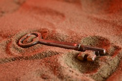 An ancient skeleton key is revealed at the surface of a sandy terrain.