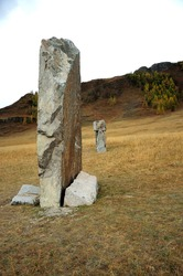 An ancient stone burial in the autumn steppe at the foot of a high hill. Karakol Valley, Altai, Siberia, Russia.
