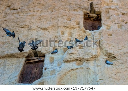 An ancient tradition, naturally cool stone carved warehouses along with many pigeon lofts for manure on a limestone cliff in Ermenek, Turkey