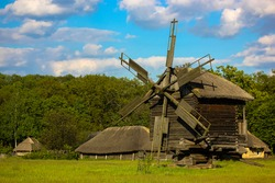 An ancient wooden mill against the background of a Ukrainian village in summer, a traditional historical houses in the open air museum Prigovo, Kiev, Ukraine. May 2019.