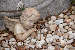 An angel rests in a garden of stones, keeping watch over someone's final resting place.