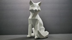 An angle cut polygon wood fox or wolf animal figure statue, painted white.