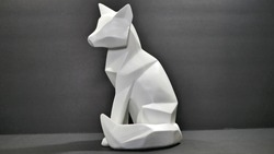 An angle cut polygon wood fox or wolf animal figure statue, painted white on a black background.