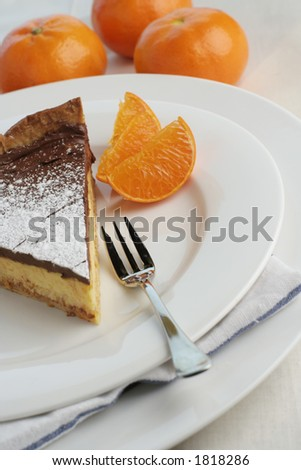 An angle view of a slice of chocolate mocha and orange cheesecake. Table setting with dessert fork and mandarin oranges for styling. Focus point on fork and top of cheesecake. Stok fotoğraf ©
