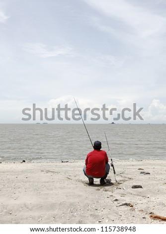 An angler fishing on a rural beach.