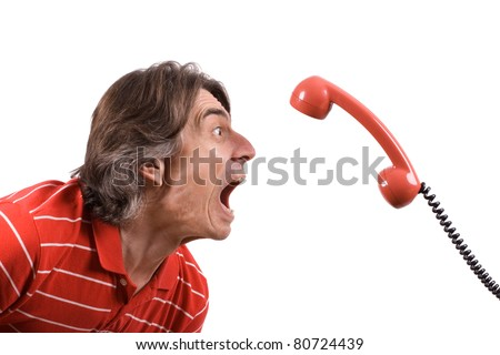An angry and irritated man screams into the telephone receiver over a white background.
