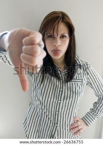 An angry business woman making a thumbs down sign with her tongue out giving a raspberry