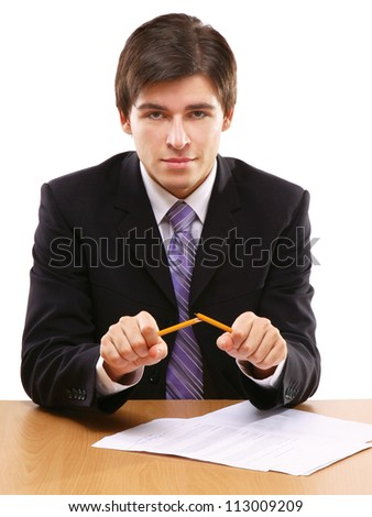 An angry businessman breaking a pencil, isolated on white