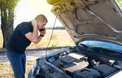 An angry man looks at the idle car engine. The driver tries to explain the cause of the breakdown to the mechanic using his smartphone and call for help. Concept of unpleasant situations on the road