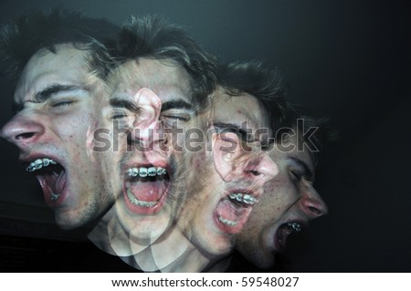 An angry man screams out of control in the darkness. He is a white Caucasian young adult wearing braces on his teeth.