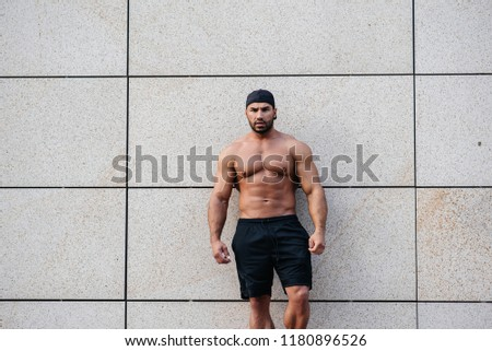 An angry sexy sportsman stands topless near the wall. Fitness, bodybuilding.