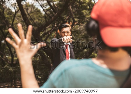 An angry young university student accuses another man of wrongdoing or a crime. Pointing his hand aggressively. The accused man holds his hands up but in denial. Foto stock ©