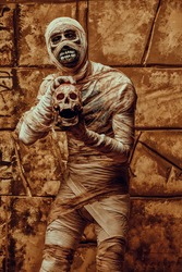 An animated mummy of a man holds a human skull in his hands. Halloween. Ancient Egyptian mythology.