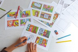 An animator painter draws a color storyboard for a comic book or movie. An illustrator seated at his desk creates a storyboard for a cartoon.