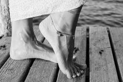 An anklet on a foot with sea view background in black and white