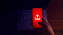 An anonymous hacker and uses a malware with mobile phone to hack password the personal data and money from Bank accounts. The concept of cyber crime.