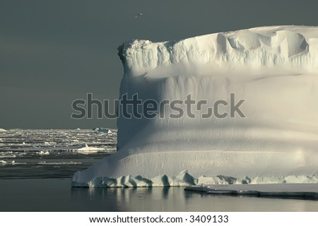 An Antarctic iceberg in the Southern Ocean on a nearly flat sea covered by ice floes. The iceberg is enlightened by the evening sun. Picture was taken during a 3-month research expedition.