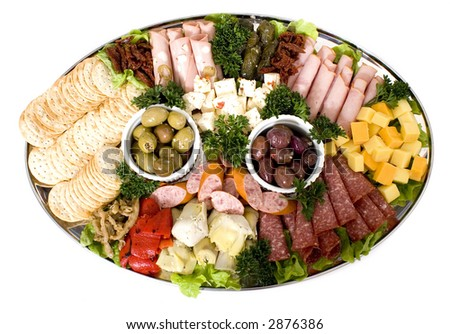 An antipasto catering platter of continental meats and feta cheese, assorted Italian delicacies, including marinated artichoke hearts, olives, sun dried tomatoes and marinated eggplant on a platter.