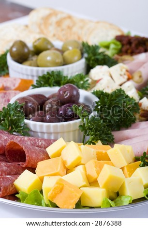 An antipasto catering platter of continental meats and feta cheese, plus marinated artichoke hearts, olives, sun dried tomatoes and marinated eggplant. Focused on the cheese.
