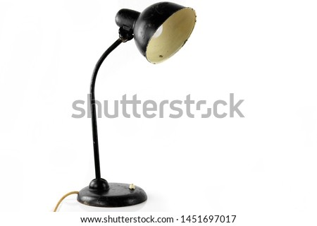 Photo of  an antique black table lamp from the 20s bauhaus era standing on an old desk worn out and damaged isolated on white background very rare in original condition design icon